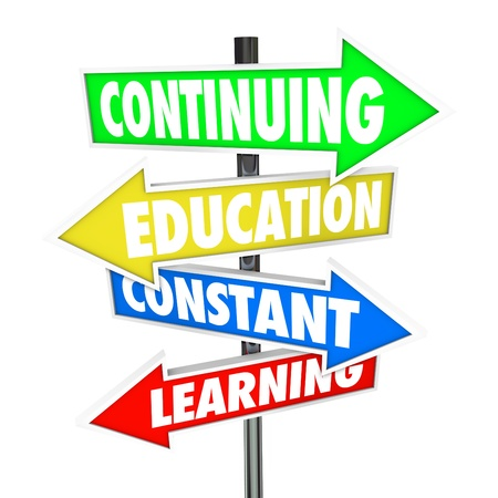 The words Continuing Education, Constant Learning on four colorful road or street signs to illustrate the importance of school and acquiring new skills and knowledge Stock Photo