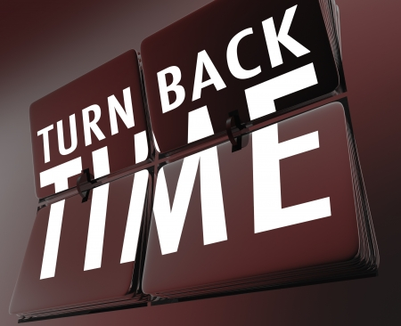reverse: The words Turn Back Time on flipping tiles on a retro clock to illustrate going backward to the past to reverse a change