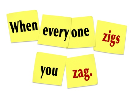 contradict: The words or saying When Everyone Zigs You Zag on yellow sticky notes to illustrate being unique, special, innovative and different to stand out from the crowd