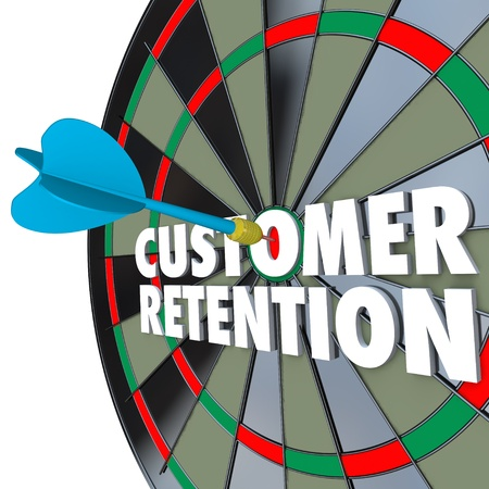 enticing: The words Customer Retention on a dartboard with a dart hitting a perfect bulls eye Stock Photo