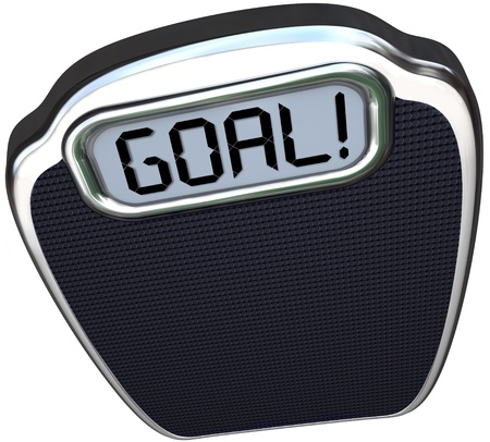 The word Goal on a scale to illustrate you have reached your target weight loss through diet and exercise and are now lighter and healthier photo