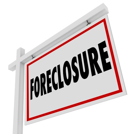 Foreclosure word on a home for sale real estate sign to illustrate failure to pay mortgage and default on a loan and the house being repossessed or reclaimed for non-payment or failure to pay Stock Photo