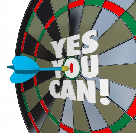 The importance of confidence and a positive attitude illustrated by a dart hitting the words Yes You Can on the bulls-eye of a dartboard photo