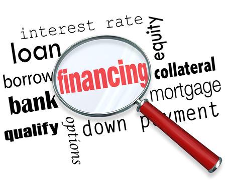 La palabra de financiación bajo una lupa con términos como tasa de interés, crédito, préstamo, el banco, los requisitos, las opciones, el pago inicial, la equidad, hipotecas y garantías Foto de archivo
