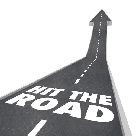 The words Hit the Road on a black pavement street or freeway to illustrate leaving or going on a trip, holiday, vacation, travel or transportation photo