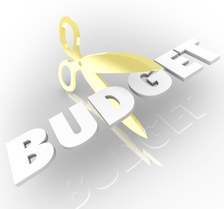 low cost: Scissors cutting the word Budget to illustrate reducing costs and returning a company or organization to financial stability and profits