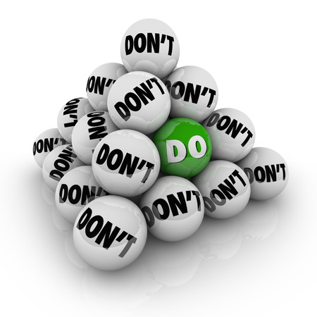 Several balls marked Dont in a pyramid and one with the word Do to illustrate permission, acceptance and a positive attitude to acheive a goal photo