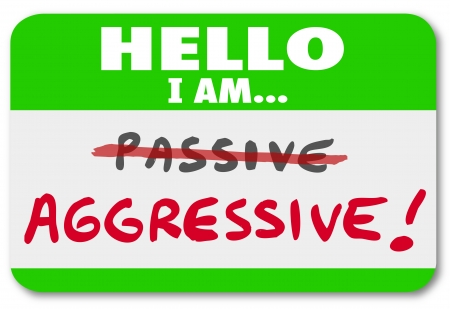 nametag: A green nametag with the words Hello I Am Aggressive and the word Passive crossed out to illustrate an attitude of ambition and go-getter outlook vs one of inaction and laziness Stock Photo