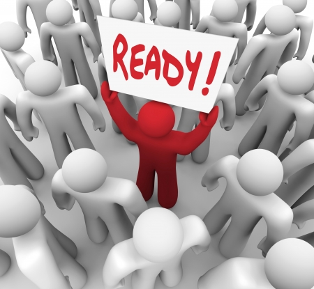 embark: The word Ready on a sign held by a unique red person in a crowd to illustrate being prepared for a test or embark on a journey or challenge Stock Photo