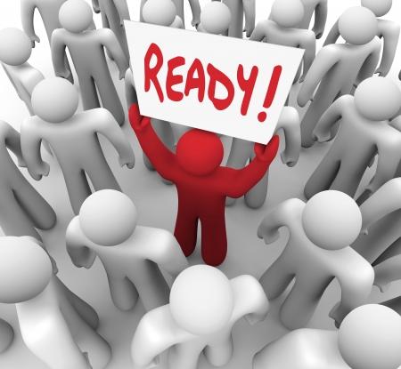 preparaba: La palabra Ready en una muestra llevada a cabo por una persona roja �nica en una multitud para ilustrar est� preparando para un examen o embarcarse en un viaje o un desaf�o Foto de archivo