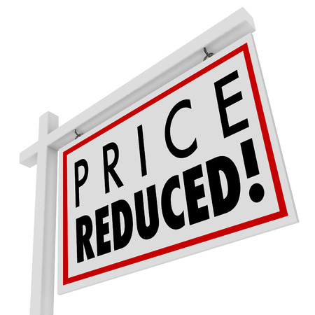low prices: Price Reduced words on a home for sale sign to illustrate a home owner in distress and needing to sell immediately as a short sale or negotiated lower value to the right buyer