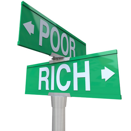 opposites: Rich vs Poor words on a green two way street or road signs pointing to poverty versus wealth to illustrate the difference between the opposites of haves and have-nots, separating the classes