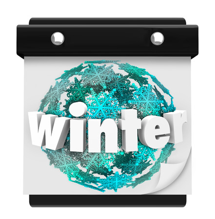 frigid: Winter word on a snowflake ball on a wall calendar page to illustrate it is the first day of the cold season, in the months December, January and February Stock Photo