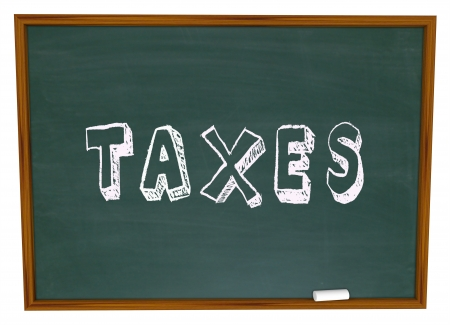 return: Taxes word written on a school chalkboard to illustrate a lesson, training, advice or other information on preparing tax returns on money earned in business or personal finance