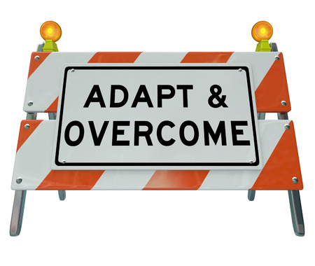 modernize: Adapt and Overcome words on a road construction barricade or sign