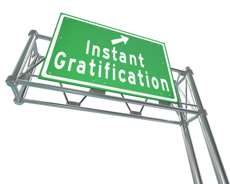 gratified: Instant Gratification words and arrow on a green freeway road sign to provide direction to quick or immediate satisfaction Stock Photo