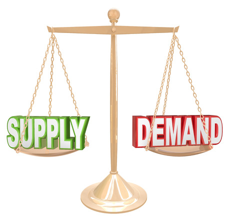 in demand: Supply and Demand words on a gold scale or balance to illustrate the principle law of a free market economy where customer needs will balance with the amount of goods supplied by sellers Stock Photo