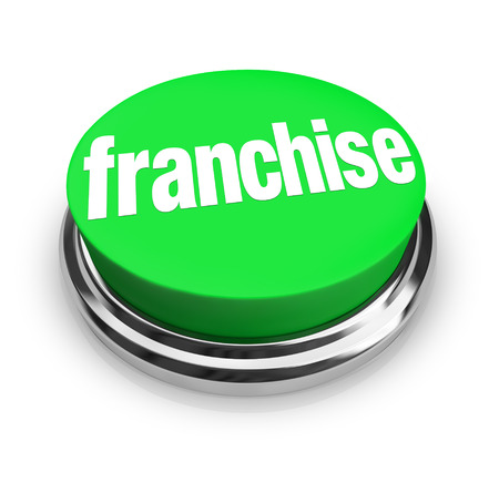 Franchise word on a large green button to press and license an established chain business for a money making opportunity for new business or start-up