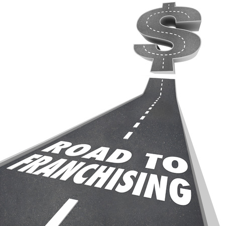 franchises: Road to Franchising words on a street or freeway leading to a large money or dollar symbol to illustrate the revenue potential of licensing a business or brand from an established chain