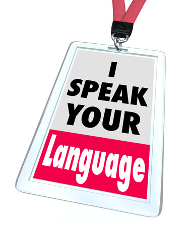 foster: I Speak Your Language words on a name badge or tag to offer translation services to foster greater communication and understanding Stock Photo