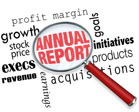 Annual Report words under a magnifying glass to illustrate searching, researching or looking for financial information on a comapny or business