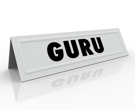 Guru word on a white tent name card to illustrate a speaker or presenter has expertise and is a master, guide or consultant in an important area or field of study