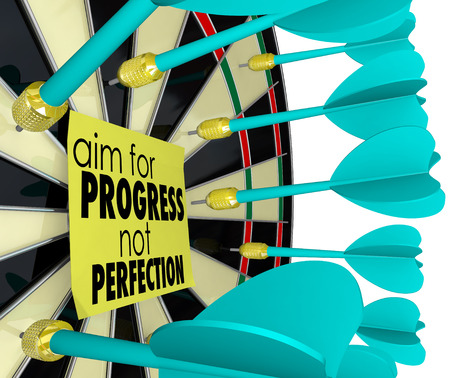 Aim for Progress Not Perfection words on a sticky note on a dart board to illustrate it is better to achieve fast improvement instead of waiting for things to be perfect before moving forward