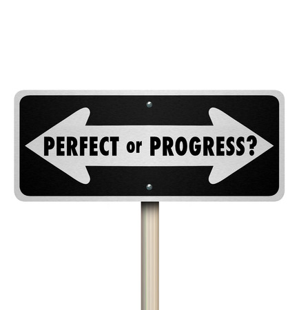 Perfect or Progress arrow road or street sign to illustrate the different opposite paths of aiming for perfection and delaying moving forward or progressing without waiting for perfection Stock Photo