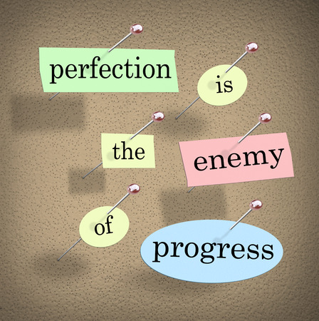 advancement: Perfection is the Enemy of Progress quote or saying with words on pieces of paper pinned to a bulletin board to illustrate you should not wait to take action until things are perfect Stock Photo