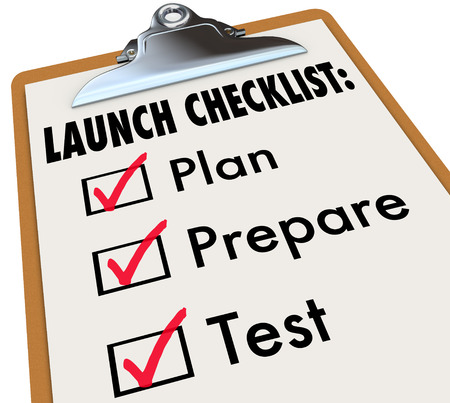launched: Launch Checklist of a clipboard with check marks in boxes to illustrate becoming ready for a start or beginning of a product, business or company debut or release -- plan, prepare and test