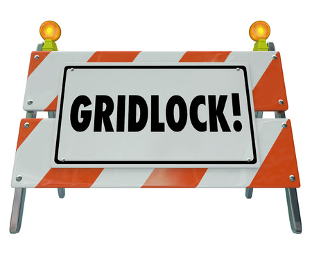 obstruction: Gridlock sign as a road construction barricade or barrier to illustrate a stoppage, obstruction, challenge, dead end or warning that movement has stopped