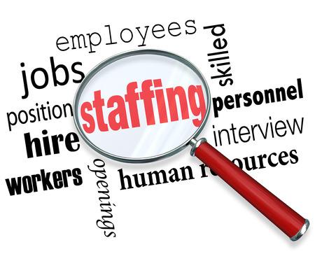 Palabras de dotación de personal bajo una lupa con términos relacionados como trabajos, puesto, trabajadores, empleados, recursos humanos y entrevistas. Foto de archivo