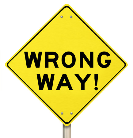 wrong: Wrong Way words on a yellow warning road sign to illustrate a bad direction you are driving down a street, based on inaccurate information or instructions Stock Photo