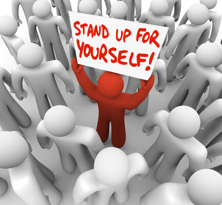 assertive: Stand Up For Yourself words on a sign held by a single man or person in a crowd to illustrate being a rebel or going on strike to protect your rights and justice