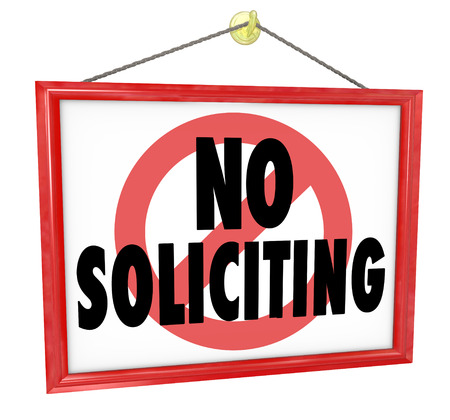 soliciting: No Soliciting sign in a home or business window to prevent unwanted and uninvited salespeople from bothering you with selling pitches