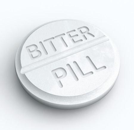forcing: Bitter Pill words on a white tablet to illustrate medicine that is difficult to swallow or an idea that is tough to take Stock Photo