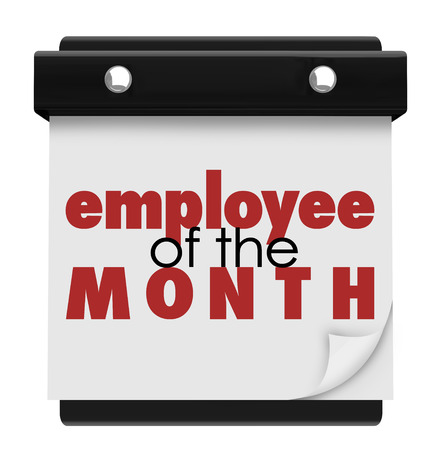 awarding: Employee of the Month words on a wall calendar or sign recognizing the top performing worker at a company or business