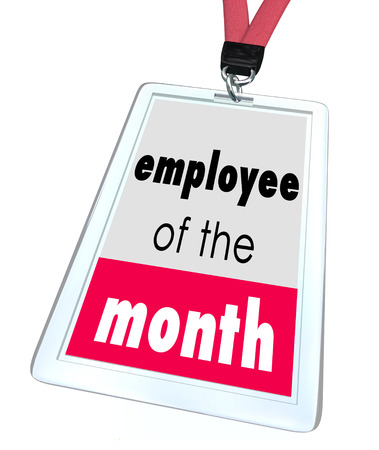 awarding: Employee of the Month words on a name tag or badge to recognize the top performing worker at a company, business, store or restaurant Stock Photo