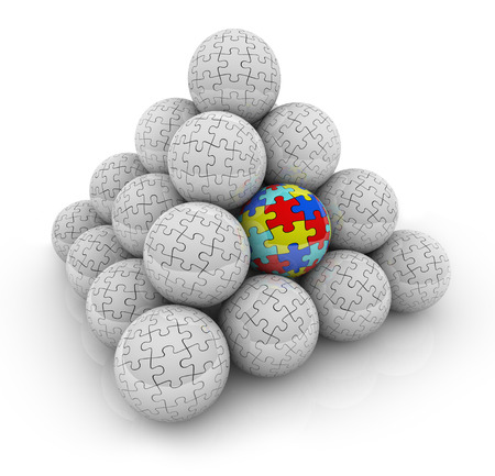 developmental disorder: A pyramid of balls with puzzle pieces on them and one with colored pieces as a symbol of autism or someone who is special, different or unique
