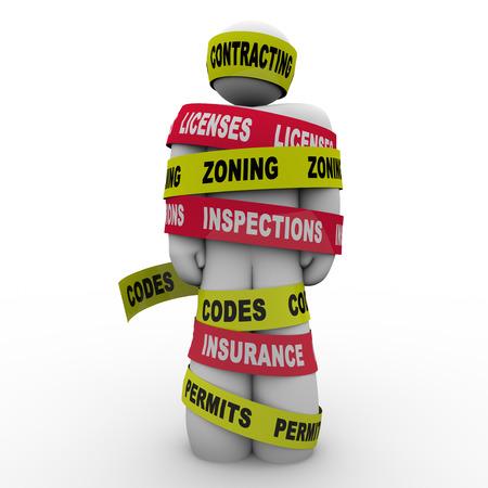 Un constructeur ou un entrepreneur enveloppé ou ligoté dans la bande contractant de lecture, de licences, de zonage, des inspections, des codes, des assurances et des permis Banque d'images
