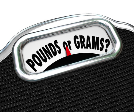 grams: Pounds or Grams words on a display of a scale to illustrate units of measure and standards for weight conversion