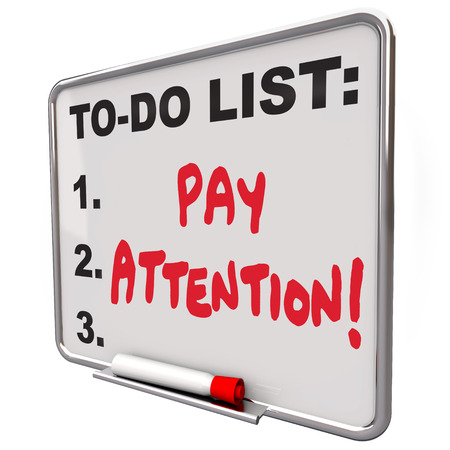 Pay Attention words written on a dry erase board telling you to watch, listen, be attentive and conscious of a lecture, lesson or the world around you