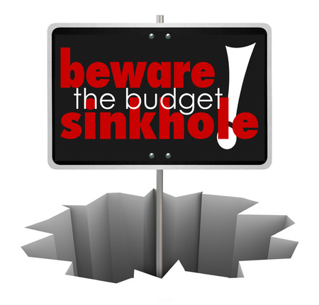 beware: Beware the Budget Sinkhole words on a sign in a hole, crack or chasm to symbolize money trouble, financial shortfall or bankruptcy Stock Photo