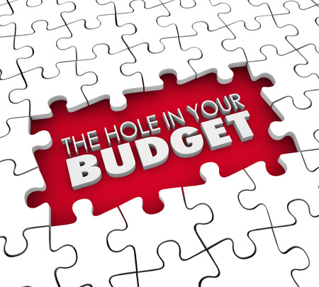 budgetary: The Hole in Your Budget words in an unfinished puzzle representing your financial trouble or problems such as bankruptcy or inability to pay bills Stock Photo