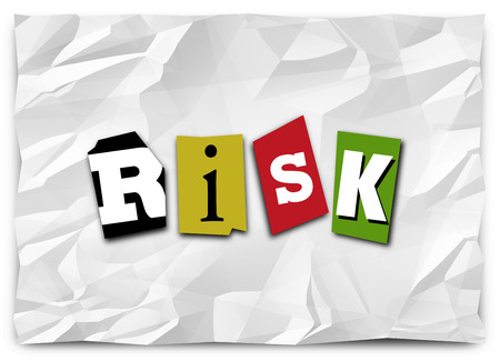 Risk word in cut out magazine letters on a crumpled piece of paper like a ransom note to warn you of a security danger or threat photo