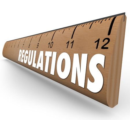 regulations: Regulations word on a wooden ruler measuring if you are within rules or guidelines for size, length or other standard