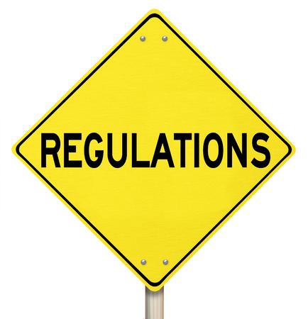 regulating: Regulations word on a yellow warning or danger road sign illustrating the perils of not following rules, laws and guidelines Stock Photo
