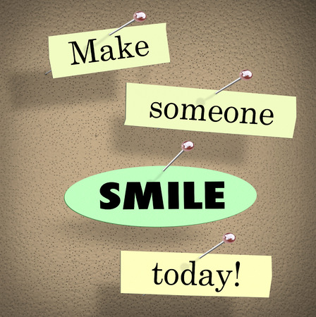 Make Someone Smile Today words on papers in a saying or quote pinned to a bulletin board Foto de archivo