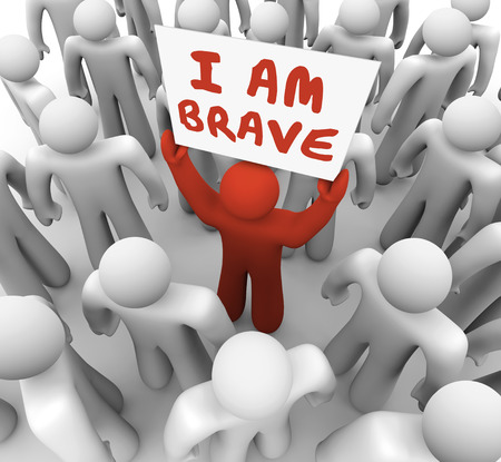 I Am Brave words on a sign held by one man in a crowd showing he is unique and different in being bold, daring, courageous and confident photo