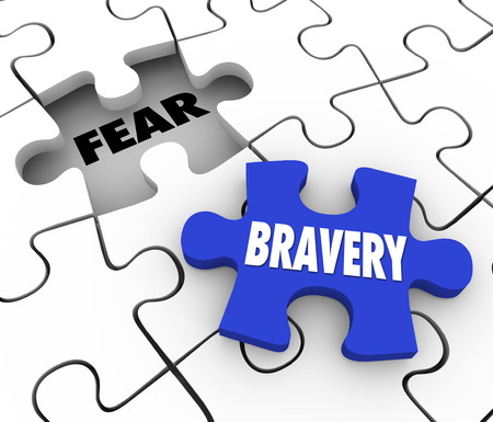 adversity: Bravery word on a puzzle piece about to fill the word Fear conquering adversity and being bold and courageous to overcome a challenge